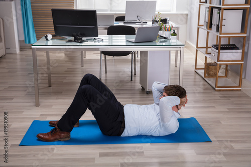 Biznesmen robi ćwiczenia na matę do ćwiczeń
