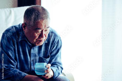 Foto Murales 窓際の椅子に座っている高齢者男性