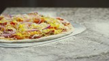 Close up shot of delicious pizza on floured surface, cook taking it with pizza peal, tracking left - 199531125