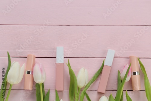 Beżowy błyszczyk i szminka kolor nago w różowe kwiaty tulipanów na różowym tle drewniane deski. Kosmetyki w pastelowych kolorach