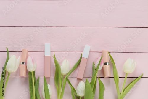 Beżowy błyszczyk i szminka kolor nago w delikatnie różowe kwiaty tulipanów na różowym tle drewnianych desek. Kosmetyki w pastelowych kolorach