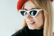 Attractive young woman in red beret and sunglasses isolated on grey