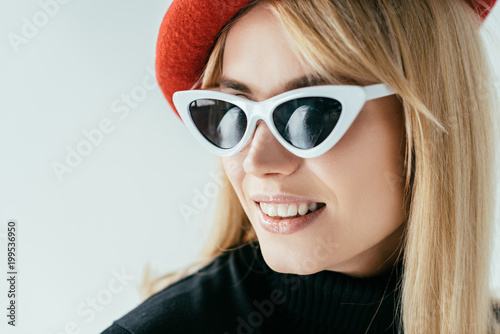 Foto Murales Attractive young woman in red beret and sunglasses isolated on grey