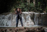 Young woman having fun under waterfalls in the forest