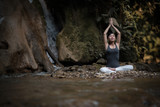 Young woman in yoga pose sitting near waterfall