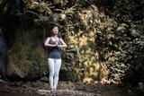 Young woman in yoga pose filing near waterfall