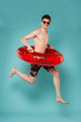 The summer, when it arrives, is the more gratefully received! Attractive young boy with naked torso jumping with rubber ring over isolated blue background.