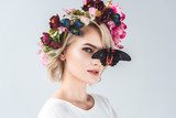 beautiful young woman posing in floral wreath with butterfly, isolated on grey - 199543770
