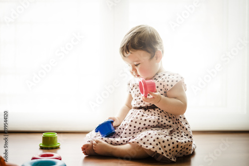 Eight months old toddler girl playing with colorful objects.