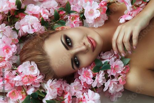 Beautiful blondie model is emotionally posing with flowers - 199549789