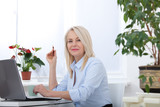 Beautiful business lady is looking at camera and smiling while working in office - 199558951