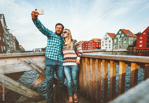 Sticker Couple in love taking selfie by smartphone traveling in Trondheim city Norway vacations weekend Lifestyle outdoor scandinavian houses landmarks architecture on background