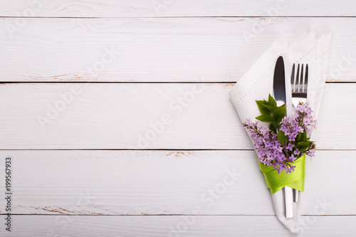 Foto Murales Spring festive table setting with vintage cutlery and lilac flowers on white wooden table,copy space flat lay