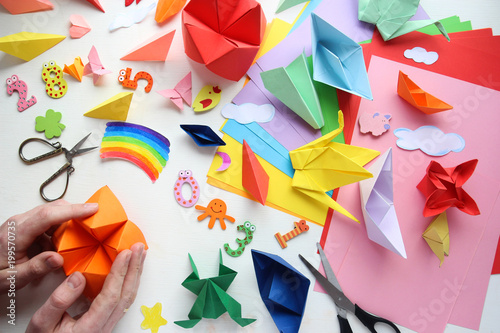 Man doing origami. Multicolored Origami and paper on  a white table. © dyageleva