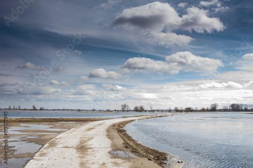 Fotobehang Donkergrijs rozlewisko rzeki , wiosenne roztopy, zachmurzone niebo