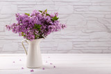 Bouquet of spring ,purple lilac flowers in a pitcher on white vintage wooden table, copy space - 199579921