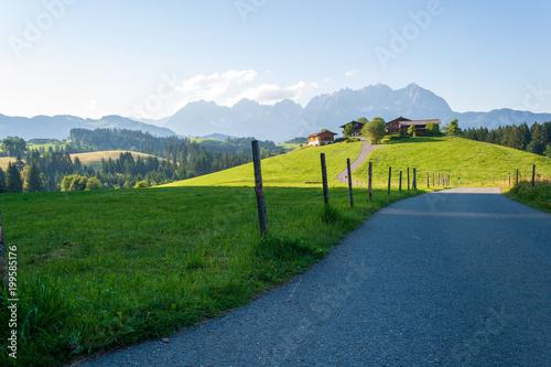 Fotobehang Blauwe hemel Wilder Kaiser mit Straße und Hügellandschaft