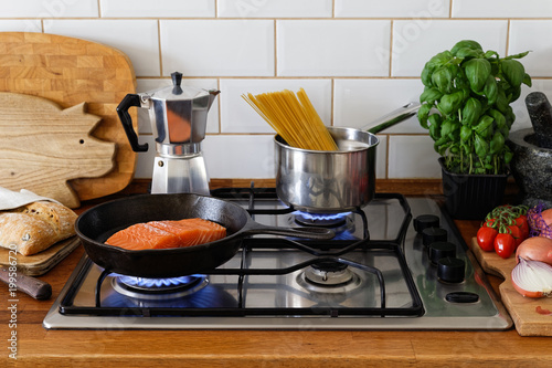 Cooking salmon fillet and spaghetti on a gas stove in traditional home kitchen. Wood worktop.
