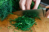 Detail of hands chopping up a bunch of dill on wood chopping board with a kitchen knife. - 199587165