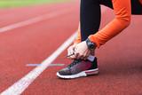 Woman runner tying shoelace on racetrack