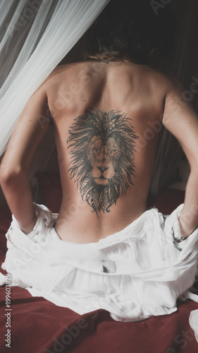 Naked back with the tattoo of a lion of a young woman sitting on a bed - 199603929