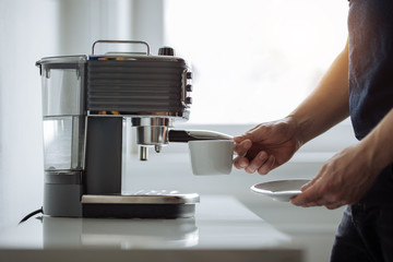 The man in the office preparing espresso coffee
