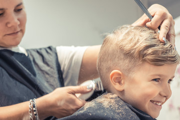 Happy kid getting haircut at hairdresser's.