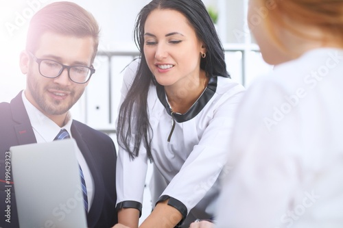 Business people at a meeting in the office. Focus on woman pointing into laptop