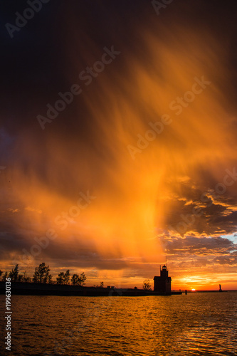Fotobehang Oranje eclat A dramatic sky over the historic Big Red lighthouse at sunset.