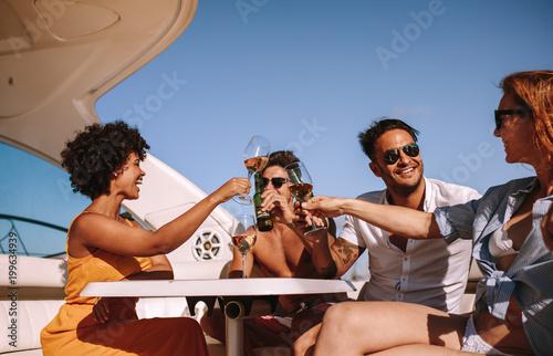 Przyjaciele bawi się na łodzi z napojami