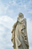 A statute of the Virgin Mary looking up while praying. - 199635755