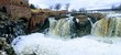 The Big Sioux River flows over rocks in Sioux Falls South Dakota with views of wildlife, ruins, park paths, train track bridge, trees and city in the surrounding area and background
