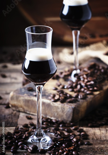 Two-layer cocktail with coffee liqueur, vintage wood background, selective focus - 199641155