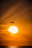 Helicopter flying against amber sky during sunset - 199642775