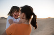 Happy daughter hugging with her mother on sand dune