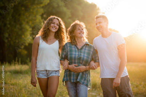 Outdoor portrait of smiling happy senior mother with her children