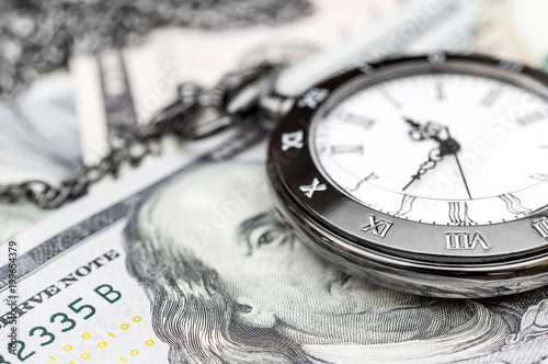 Pocket watch on dollar bills. Close up.