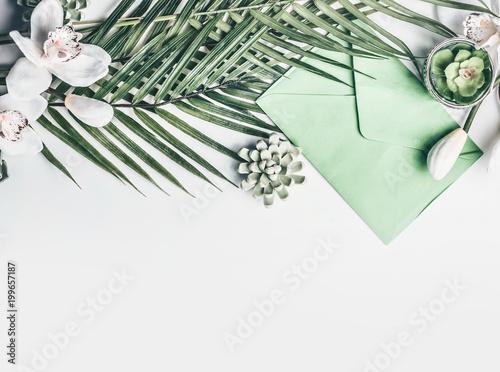 Zieleni Tropikalni liście z storczykowymi kwiatami, kopertą i sukulent dekoracją na białym desktop tle, odgórny widok, graniczą
