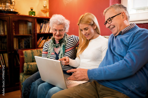 Young woman pointing on computer and showing to grandparetns images