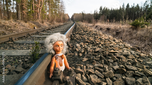 Broken abandoned doll on train rail in sunny forest landscape. Lost child toy at the old rusty railroad track. The concept of danger, childhood, fate, accident, science fiction, war or abuse.