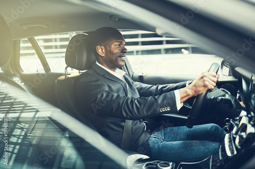 Smiling African businessman commuting to work in his car