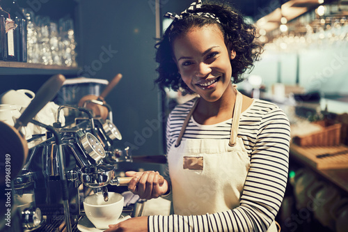 Young African barista making fresh coffee in a cafe