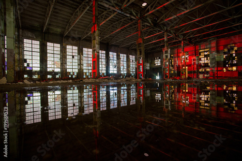 Aluminium Gebouw in Puin Flooded abandoned large industrial hall illuminated by red lights. Reflection in water. Abandoned Voronezh excavator plant