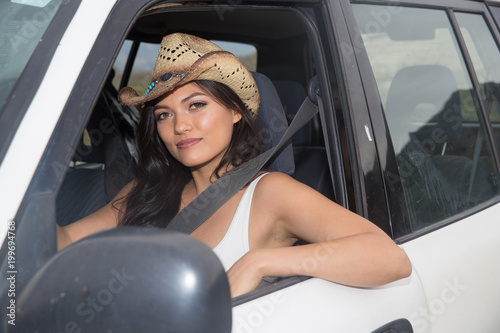 Foto Murales Pretty woman wearing cowboy hat in car