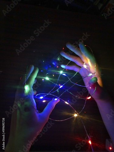 Garland of colorful lights in hands on a dark background - 199695738