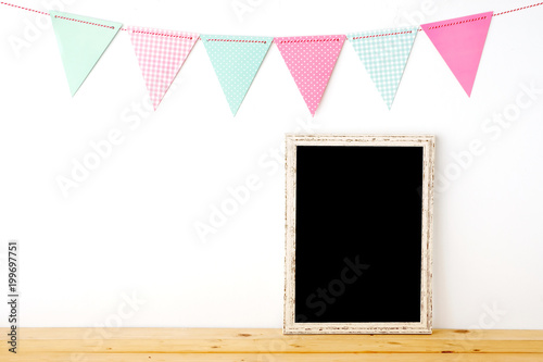 Foto Murales Colorful party flags hanging over blank white vintage wooden frame on wood table background, birthday, anniversary, celebrate event, festival background