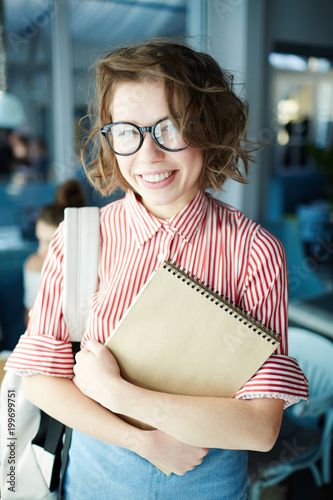 Cute student in eyeglasses and casualwear looking at camera with smile in cafe after classes