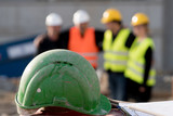 Green safety hardhat on foreground. Group of four construction workers posing on an out of focused background - 199701185