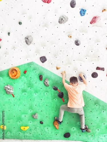 Zdjęcia na płótnie, fototapety, obrazy : boy climbing rock wall