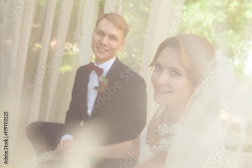 szczęśliwi nowożeńcy trzymając się za ręce i siedząc na beżowej kanapie w parku